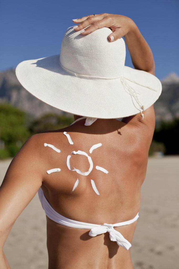 Tanning lotion in the shape of sun on woman's shoulder.